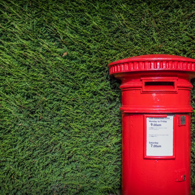 Red British post box set against a hedgerow