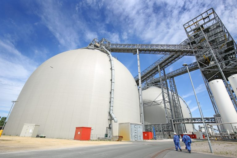 Engineers walking in front of sustainable biomass wood pellet storage dome at Drax Power Station, June 2021